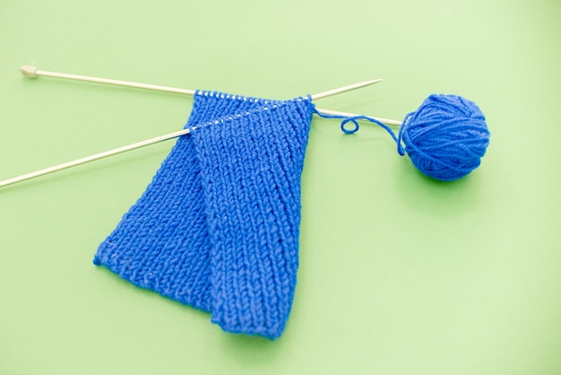 Bright blue scarf with knitting needles light  green background.