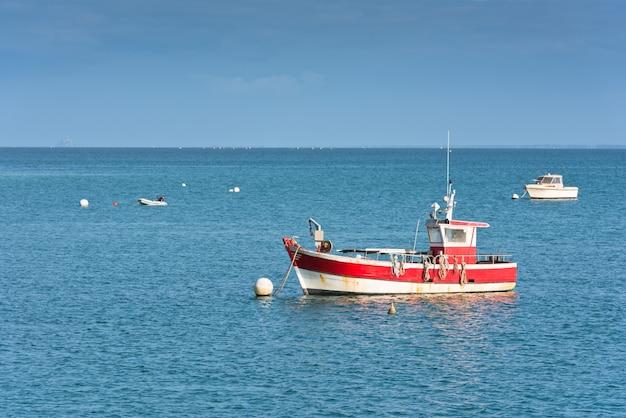 明るい青い海とブルターニュ、フランスの漁師船