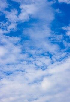 흩어져있는 흰 구름 세로보기와 밝은 푸른 하늘