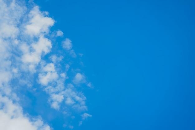 白い雲と明るい青い空。青色の背景にテキストを配置します。