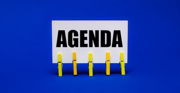 On a bright blue surface on yellow clothespins, a white card with the text agenda.