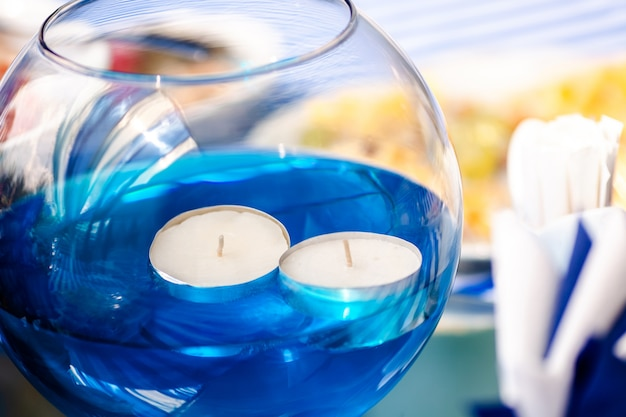 Bright blue water with candles in the glass vase and wooden toy ship