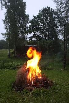 Яркое пламя костра на сельском поле вечером