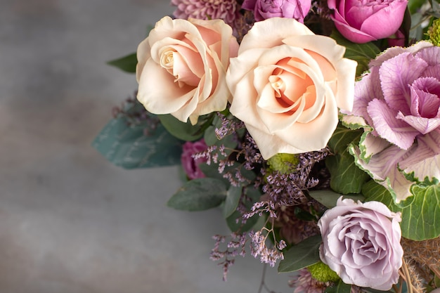 Bright bouquet of different varieties of roses with a rosette of brassica on a gray background. horizontal image, copy space