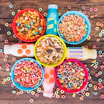 Bright bowls of cereals with milk bottles on table