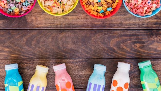 Bright bowls of cereals with milk bottles