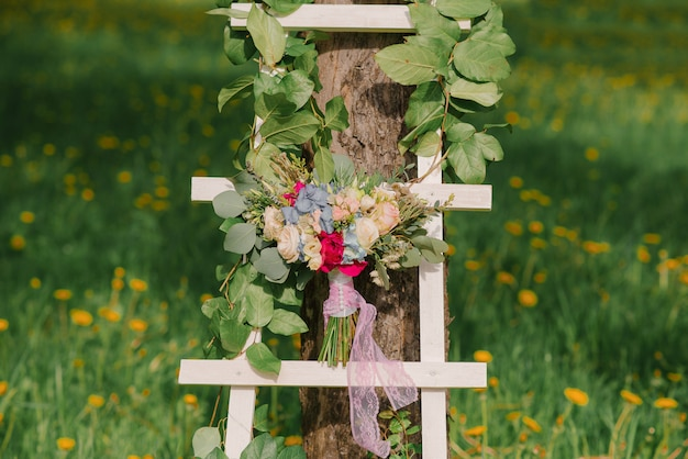 Bright bride's bouquet on a white stepladder on green grass
