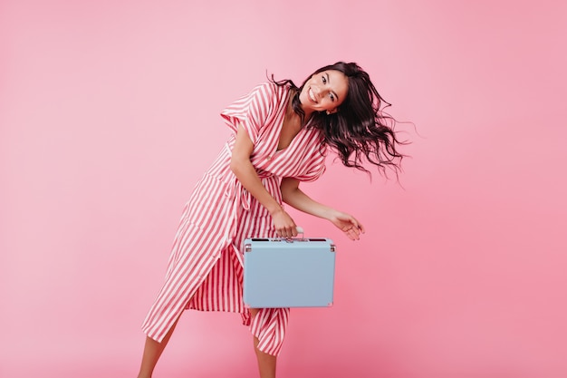 Bright brunette with brown eyes dances and plays hair, posing with blue suitcase.