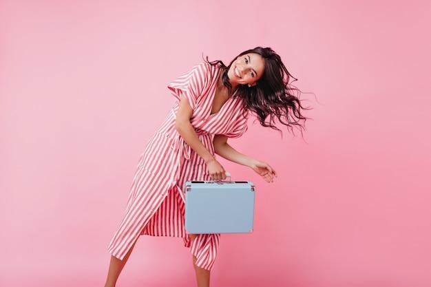Bruna brillante con gli occhi marroni balla e gioca con i capelli, in posa con la valigia blu.