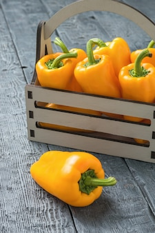 Bright bulgarian pepper in a wooden box on a wooden table. vegetarian food. a fresh crop of vegetables.