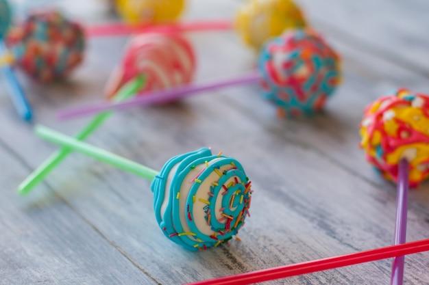 Яркие конфеты на палочке. торт поп на серой поверхности. белый шоколад и голубая глазурь. купите угощения для детей.