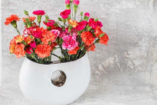 Bright carnations in a vase on a gray background. free space for text