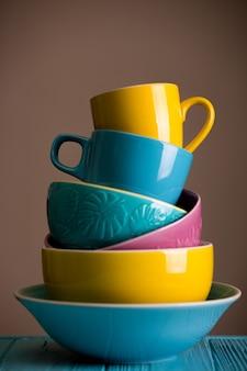 明るい陶器-青、黄、ピンクの色のカップとボウル