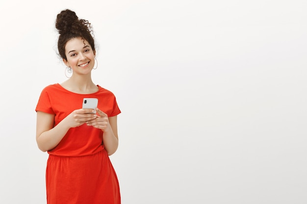 Bright charming curly-haired female in cute red dress smiling broadly and tilting head while holding smartphone and sharing tender message with friends