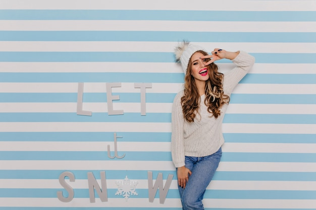 暖かいウールのセーターと白いニット帽をかぶった明るく陽気で魅力的な女性は、見て楽しんでいます。