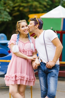 Bright cheerful couple in love resting in an amusement park.