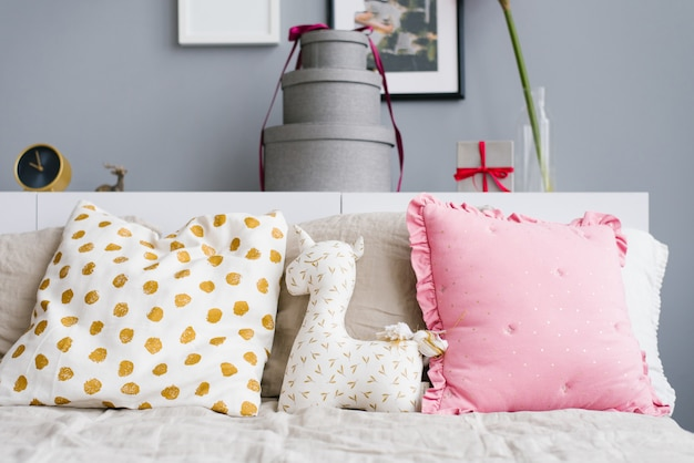 Bright cheerful pillows, unicorn pillow on the bed decorated for christmas