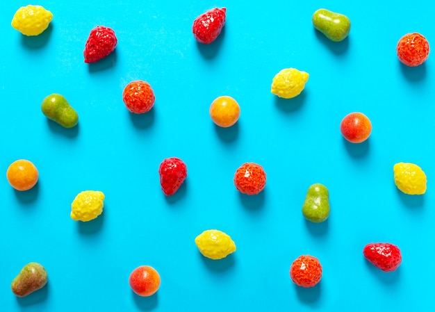 Bright chewy candies in the shape of fruits scattered on a blue background. top view. creative sweets background.