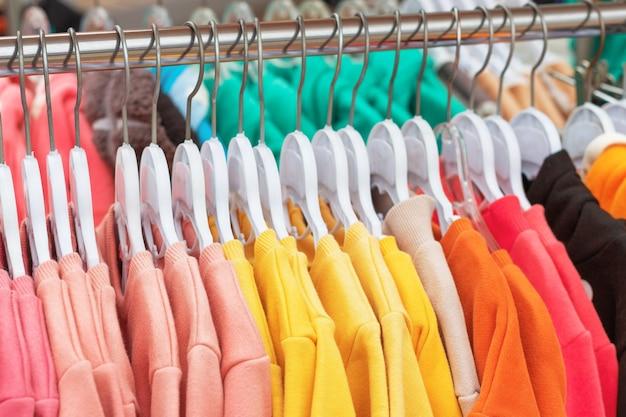 Яркая детская одежда на вешалках в магазине крупным планом.