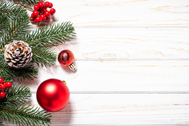 Bright christmas banner with fir tree branches and red balls on white rustic background
