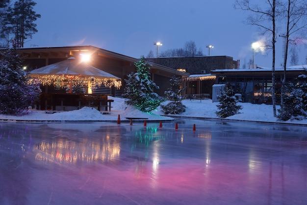 通りのアイススケートリンクの明るいクリスマスコーヒーショップ