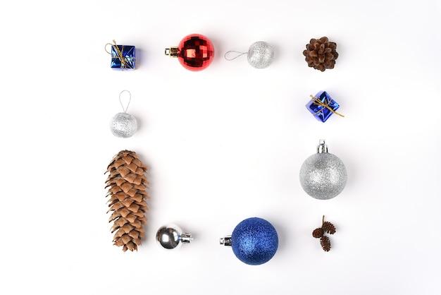 Яркая новогодняя рамка из шишек и елочных игрушек разного цвета на белом фоне пространство для копирования зимние праздники новый год