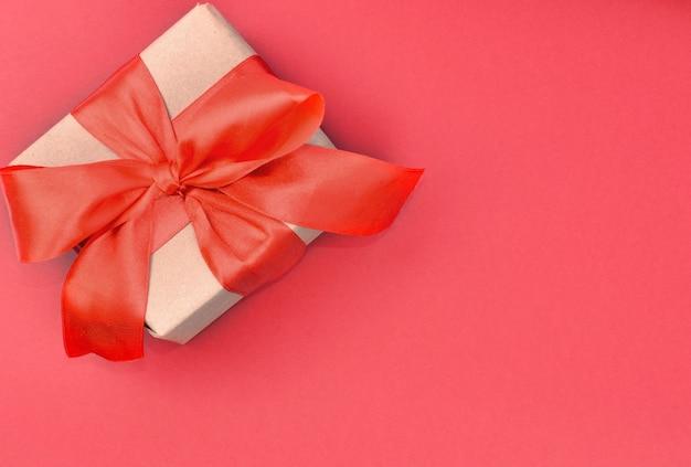 밝은 크리스마스, 새 해, 발렌타인 선물, 빨간 리본, 흰색 배경에 고립 된 공예 종이로 만들어진. 목업. 인사말 카드, 평면 누워. 공간을 복사하십시오.
