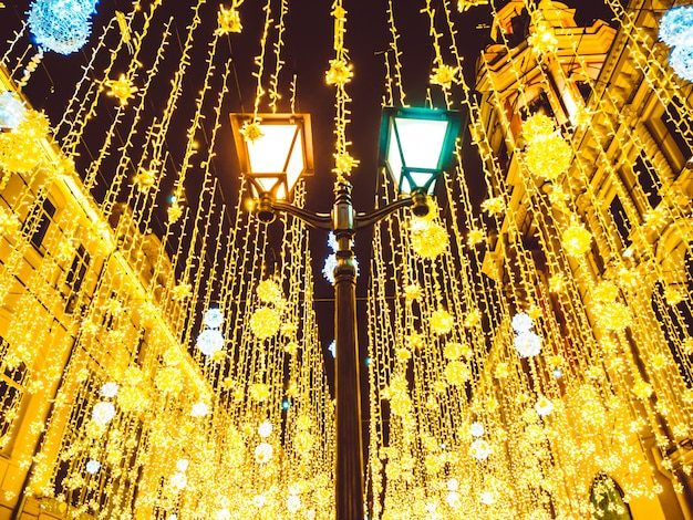 Bright christmas street illumination on the facade of the buildings.