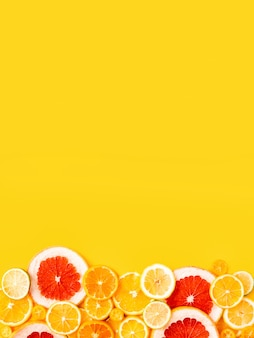 Bright citrus fruits on a yellow background, summer flat lay concept.