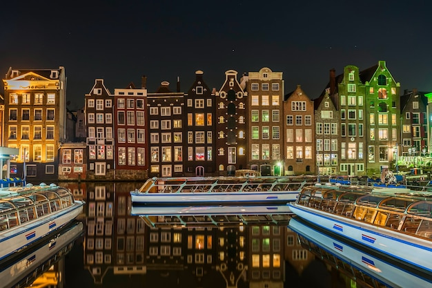 Bright cityscape of amsterdam with night lights reflection in water