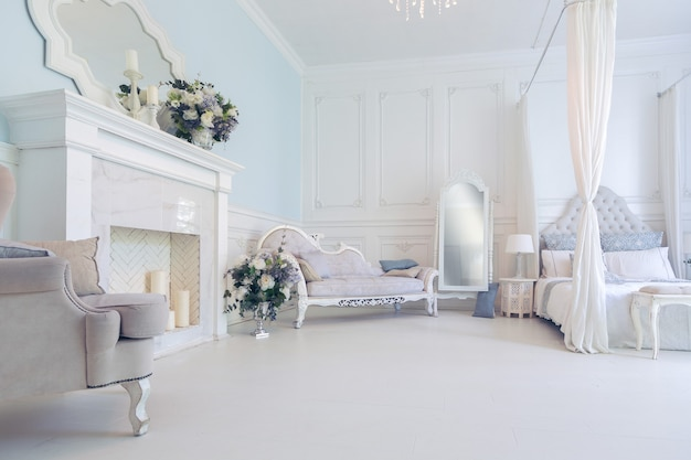 Светлый, чистый стильный интерьер спальни и гостиной с большим панорамным окном. красивая богатая антикварная мебель. кровать с балдахином, зеркало и диван.