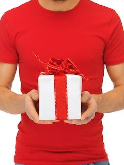 선물 상자를 들고 남자의 손의 밝은 근접 촬영 사진.