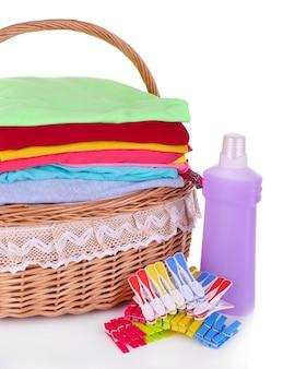 洗濯かごの中の明るい服、ピン、洗濯用シャンプー付きボトル、白で隔離