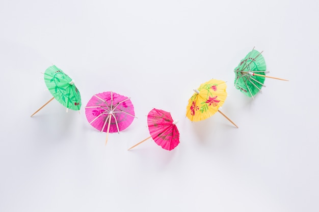 Bright cocktail umbrellas on white table