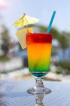 Bright cocktail with umbrella on the background of the pool