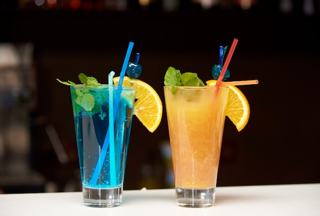 Bright cocktails on a bar counter against a dark background.