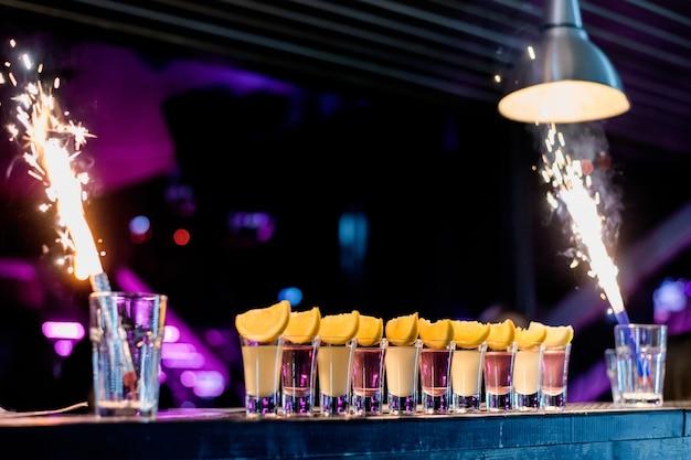バーでの明るいカクテルショットナイトクラブでのカラフルな映像 Premium写真
