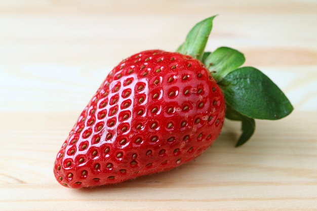 Bright color fresh ripe strawberry isolated on wooden table