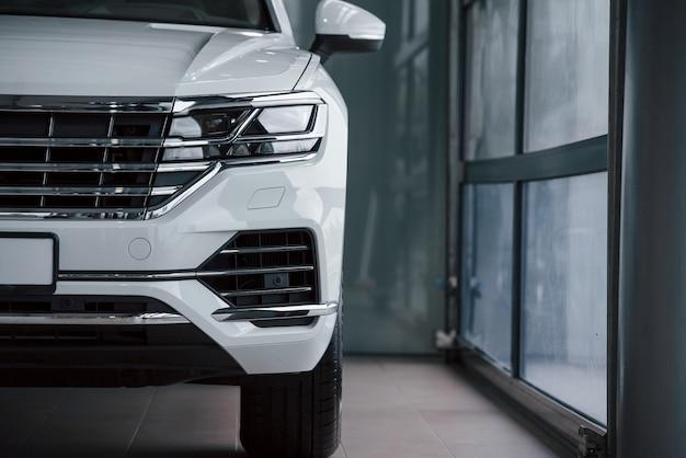 밝은 색. 낮에 실내에 주차 된 현대적인 고급 흰색 자동차의 입자보기
