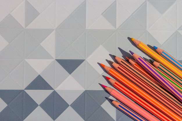 Bright color pencils on modern low poly, polygon geometric abstract background.