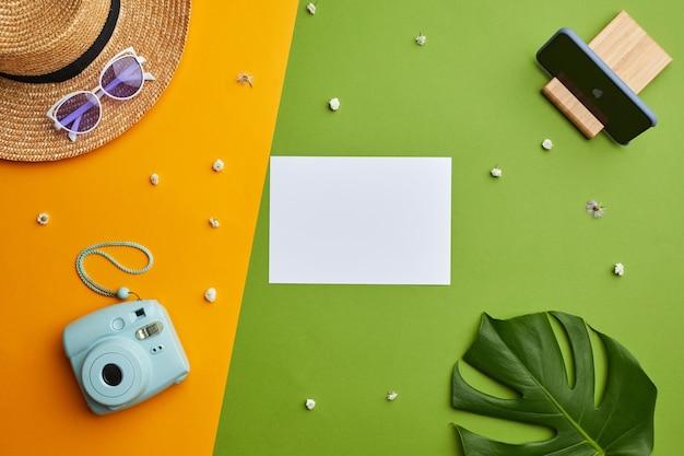 休暇の雰囲気とグラフィックの熱帯の背景上の空白の白い紙とインスタントカメラの明るい色のポップ構成、