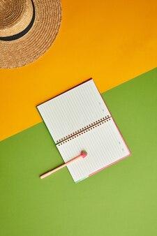 グラフィックの熱帯の背景の上に麦わら帽子とオープンプランナーの明るい色のポップ構成、