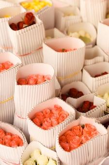 흰 종이에 싸인 밝은 색 장미