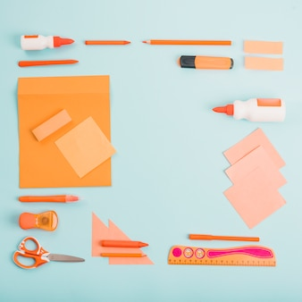 Bright color school accessories arranged on blue backdrop