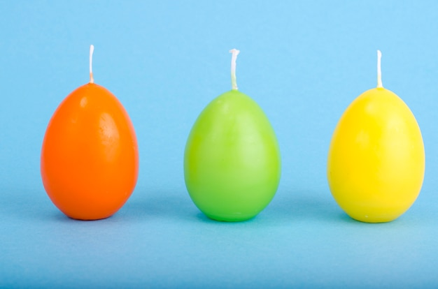 Bright colored decorative candles in shape of eggs.