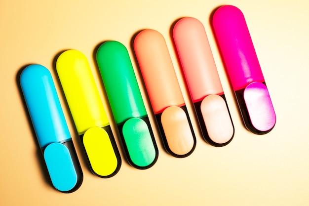 Яркие цветные маркеры для выделения текста на бежевом фоне, цветные фломастеры для рисования.