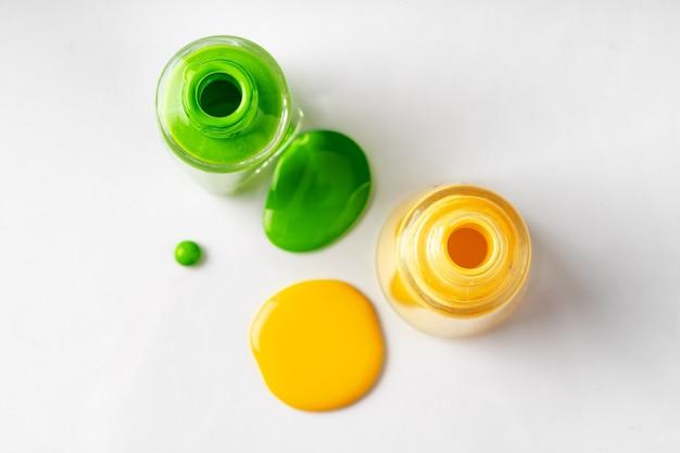 Яркие цветные бутылки лака для ногтей с каплями на белом фоне