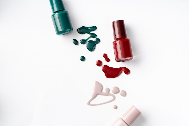 Bright colored nail polish bottles with drippings on white surface