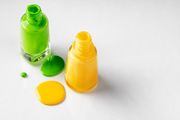 Bright colored nail polish bottles with drippings on white
