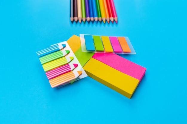 明るい色の鉛筆は、中央の青い壁の右上隅に並んで配置され、その中央には多くの異なる色のステッカーが山に積み上げられています